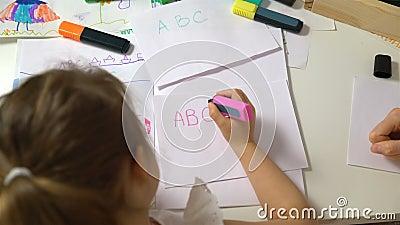 Petite fille apprenant à écrire l'alphabet Tir de chariot banque de vidéos