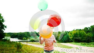 Petite fille avec des ballons dans le parc banque de vidéos