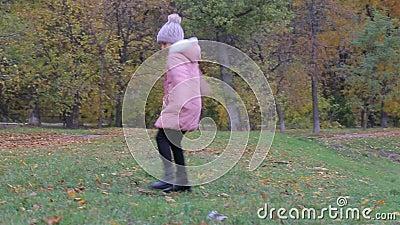 Petite fille en automne de parc Sourires adorables de petite fille banque de vidéos