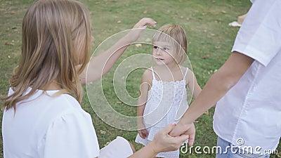 Petite fille mignonne tenant la main de ses parents dans le parc Joyeux enfant passé du temps en famille Enfance, parentalité banque de vidéos