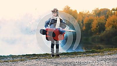 Petite position heureuse de fille d'aviateur près de lac dans le costume plat de carton avec de la fumée bleue de couleur jouant  banque de vidéos