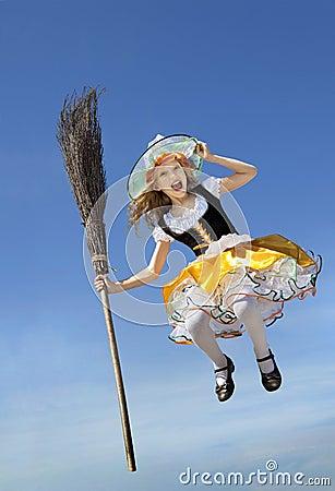 petite fille motive mignonne dans un costume de sorcire avec un balai volant haut au dessus de la terre au ciel bleu