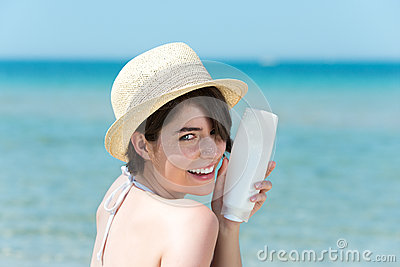 Petty woman with a bottle of sun cream