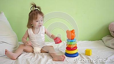 Peu d'enfant récupère dans l'installation médicale, s'assied sur le lit et joue en cubes et pyramide et sourires doux colorés banque de vidéos