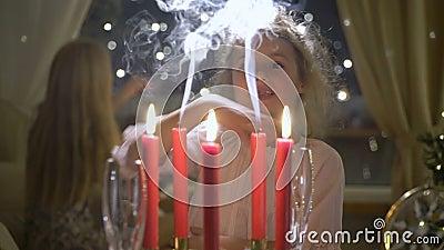 Peu fille soufflant les bougies rouges de Noël banque de vidéos