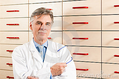 Pharmacist in front of medicine chest