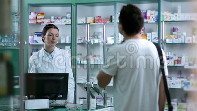 Pharmacist giving advice to customer on medication stock video footage