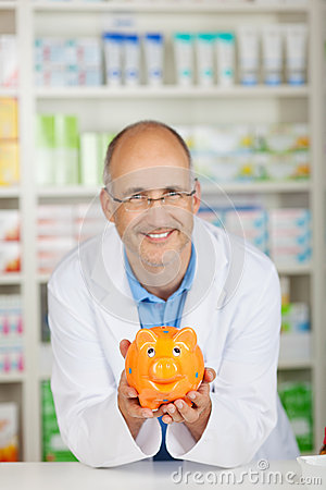 Pharmacist holding piggy bank
