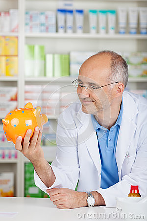 Pharmacist Holding Piggybank While Leaning On Counter