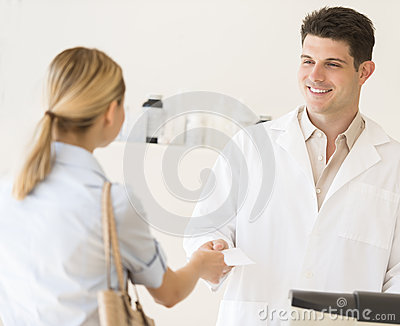 Pharmacist Receiving Prescription Paper From Customer At Store