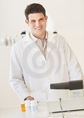Pharmacist Smiling While Standing At Counter In Drug Store
