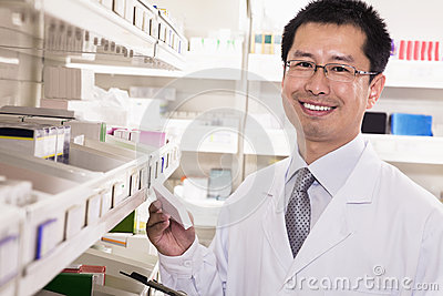 Pharmacist taking down and examining prescription medication in a pharmacy, looking at camera