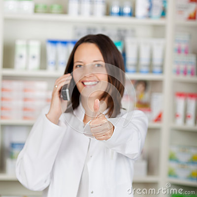 Pharmacist Using Landline Phone While Gesturing Thumbsup
