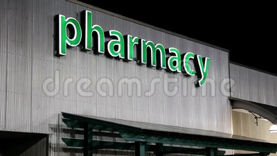 Pharmacy sign on building. At night scene stock video