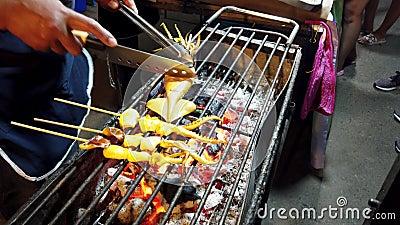 Phayao, Thailand - 2019-03-08 - Nahrungsmittelverkäufer schneidet Kalmar auf Ofen stock footage
