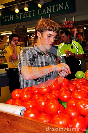 Philadelphia, PA: Young Man Buhying Tomatoes Editorial Stock Image