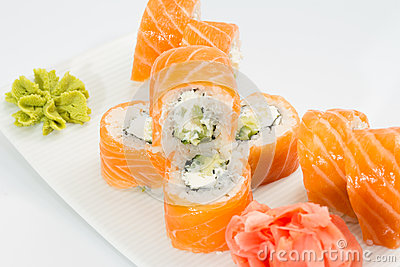 Philadelphia sushi roll with ginger and wasabi on white plate