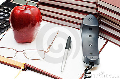 Phone, apple and glasses on the book