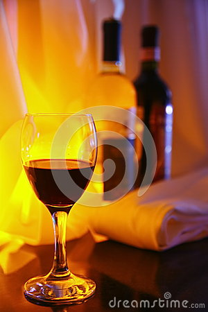 Free Photo-filled Red Wine Glass Transparent Glass On The Background Of Two Full Bottles Of Red And White Wine. Royalty Free Stock Images - 53806209