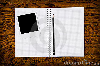 Photo frame on blank notebook with pencil