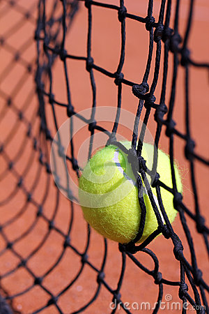 Photo of new tennis ball struck in net