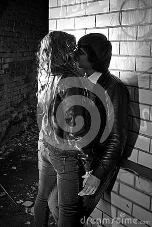 Photo of sexy couple hugging near brick wall at night