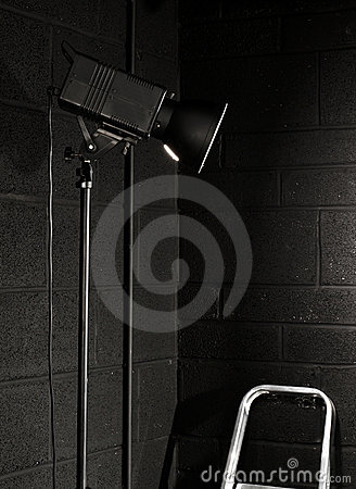 Photography studio light against a black brick wal