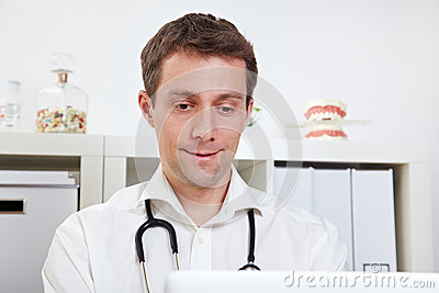 Physician with laptop in office