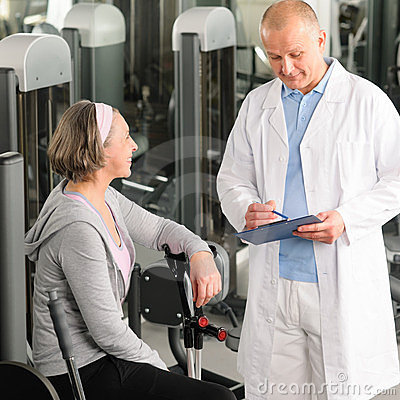 Physiotherapist assist active senior woman at gym
