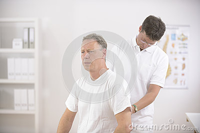 Physiotherapist examining senior man man