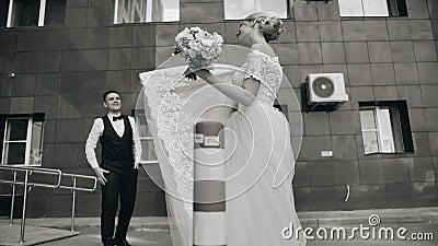 Piękna dziewczyna w białej sukni figlarnie huśta się oblamowanie jej suknia przed jej chłopakiem Jej chłopaków spojrzenia przy on zbiory