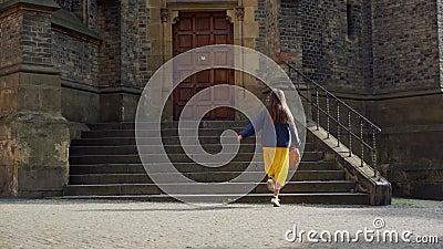 Piękna dziewczyna w spódnicy kręci się ze szczęściem w pięknym słońcu w tle gotyckiej architektury zbiory wideo
