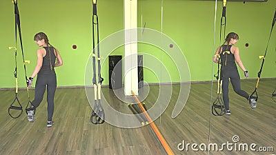 Piękna dziewczyna wykonuje TRX zawiasu ćwiczenia w nowożytnym gym, siły szkolenie zbiory wideo