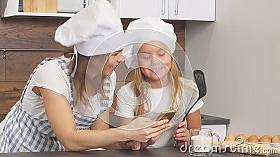 Piękna matka i córka patrzą na siebie z miłością, idą piec w kuchni zbiory wideo