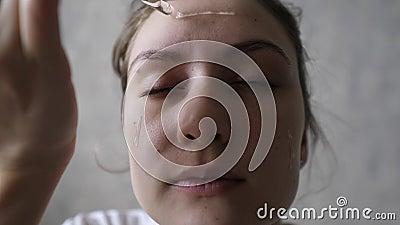 Piękno i opieka osobista - zdrowa kobieta przykleja do twarzy pipetą surowicę Naturalny produkt kosmetyczny z zdjęcie wideo