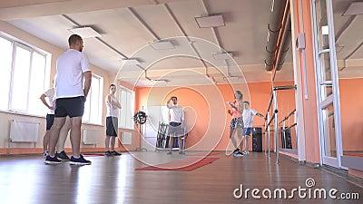 Piękny caucasian dziewczyna trener w gym wyjaśnia faceci w gym poprawność ćwiczenia w parze zbiory