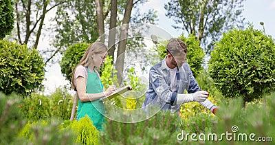 Piante d'esplorazione dell'uomo e della donna in giardino botanico video d archivio