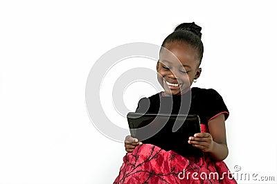 Piccola ragazza afroamericana che per mezzo di una compressa digitale