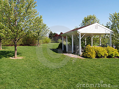 Picnic pavilion by a green lawn and trees