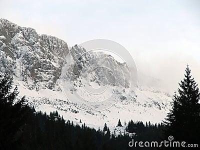 Picos de montanha cobertos por nuvens e por neve