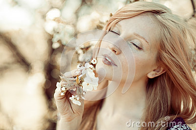 Picture of beautiful woman inhales the smell of spring