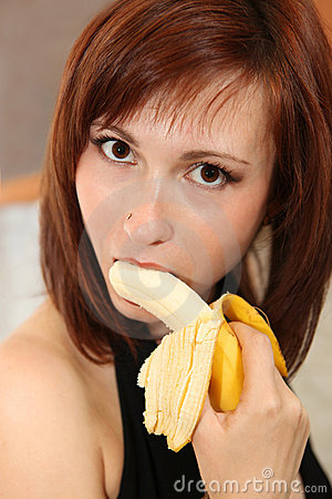 Picture of young woman eating banana