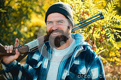 Pictures for Barbershop. Bearded hunter man holding gun and smile. Hunter with long beard on hunt. Barbershop vintage Stock Photo