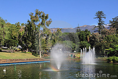 Picturesque lake with fountains and a rainbow