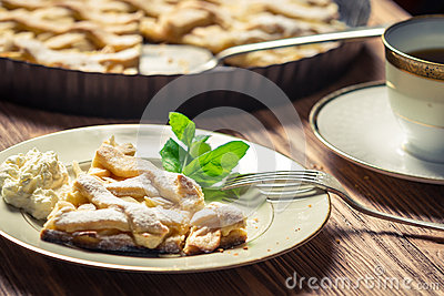 Piece of apple pie with cream on a plate