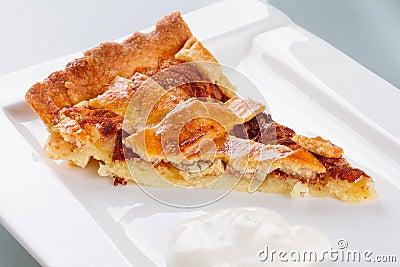 Piece of apple tart and cream on plate