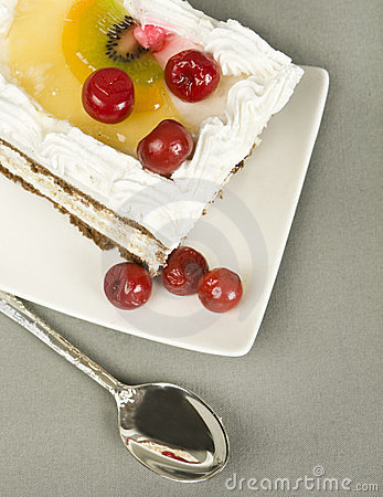 Piece of cake with  cherry on  saucer and tea