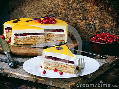 Piece of cake covered with a mirror coating, decorated with cranberries and chocolate decor. Modern Russian honey cake. Stock Photo
