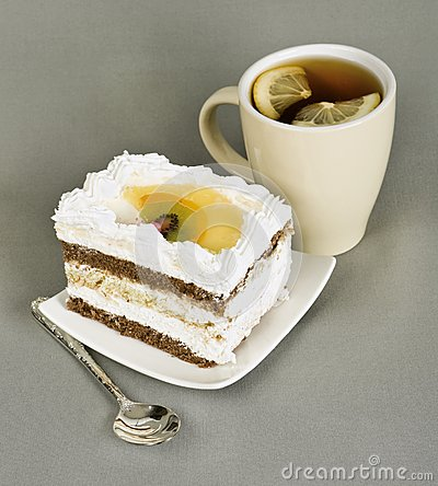 Piece of cake with fruit, tea with , spoon