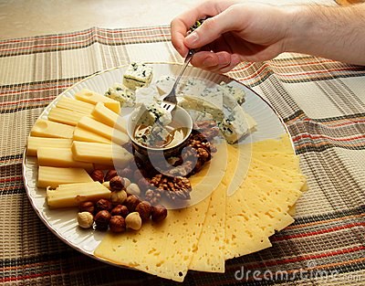 A piece of cheese on a fork in the man s hand and ran down with his honey